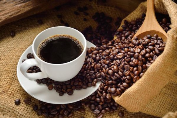 Cup of coffee on a table, in a white cupe, with coffee beans and a coffee hessian bag in the image too
